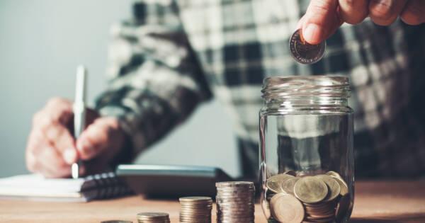 Man Saving Coins in Money Jar