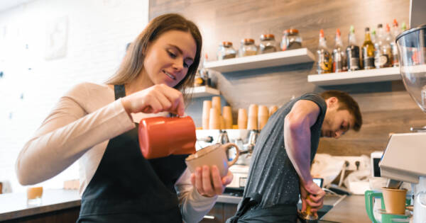Woman Working as a Barista Pouring Coffee