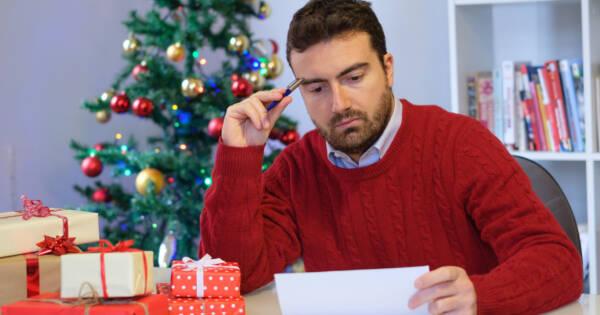 Man Upset Looking at Bills with Christmas Tree