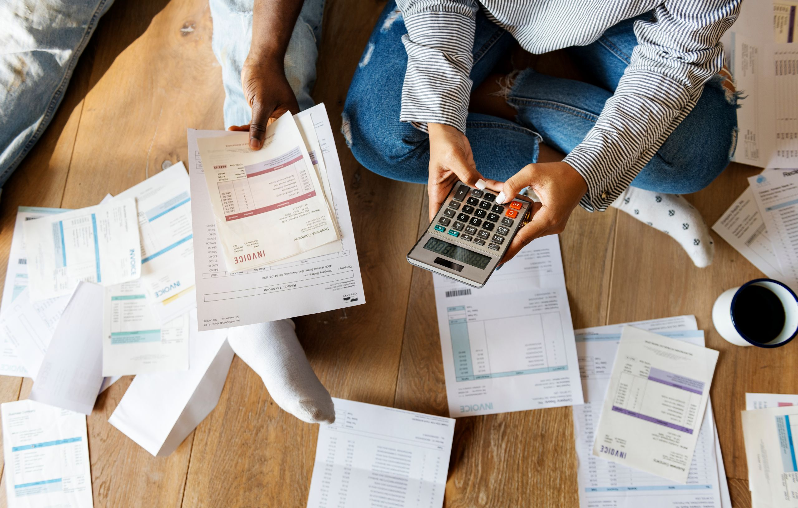 Calculating Debt with Invoices on Wood Floor