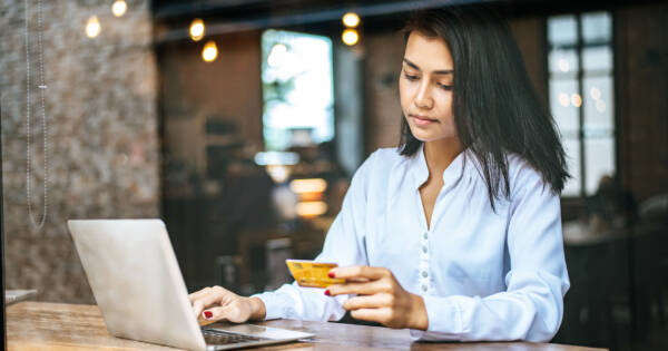 Woman with Laptop Looking Sad at Credit Card