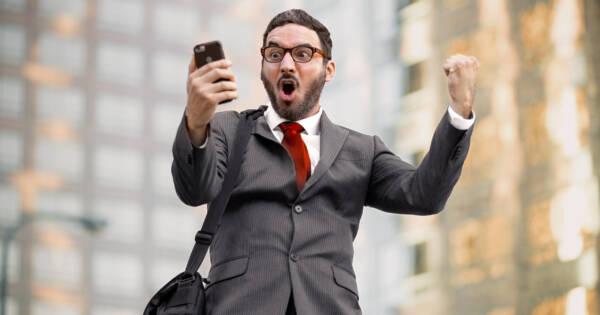 Investor Celebrating Looking at Mobile Phone