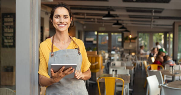 Restaurant Owner Looking at Online Business Resources on Tablet