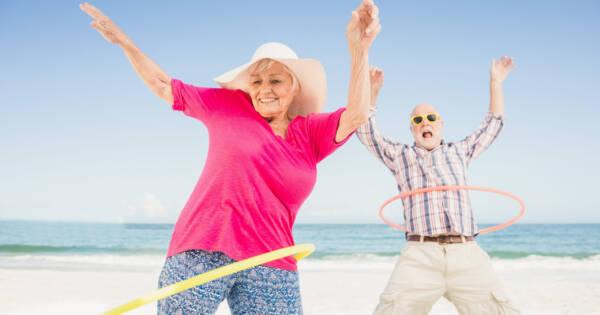Retired Couple Hula Hooping on Beach