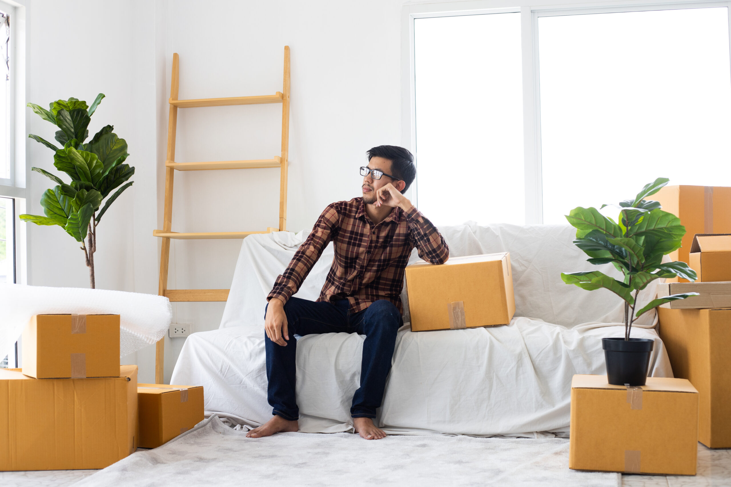 Man Sitting in Room of Moving Boxes